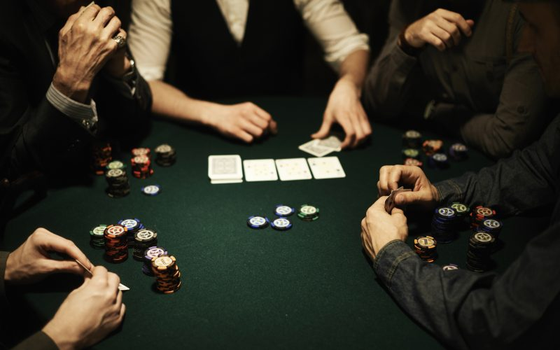 Players' hands, stacks of gambling chips and cards on poker table